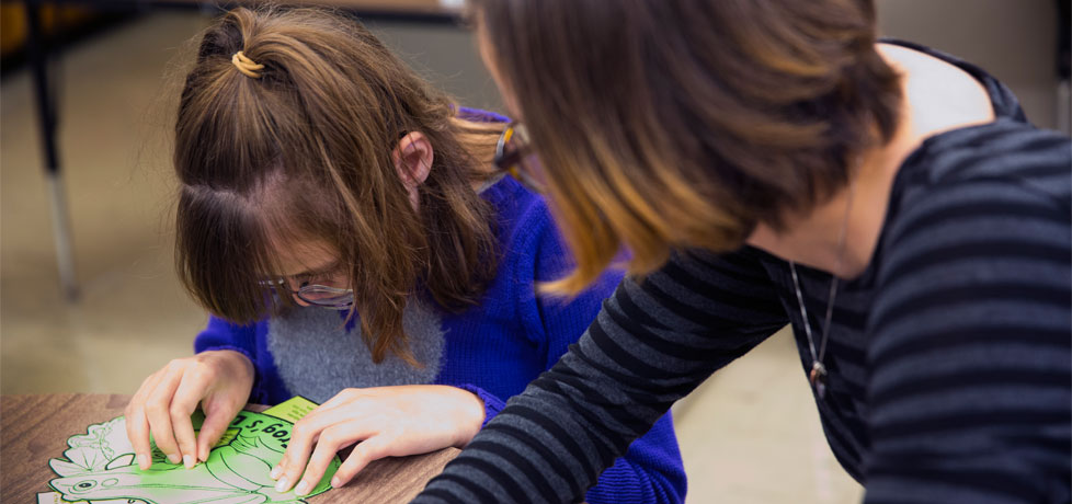 A teacher assists a student with an assignment.