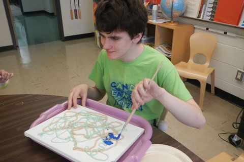 A student creates a mixed media art project.